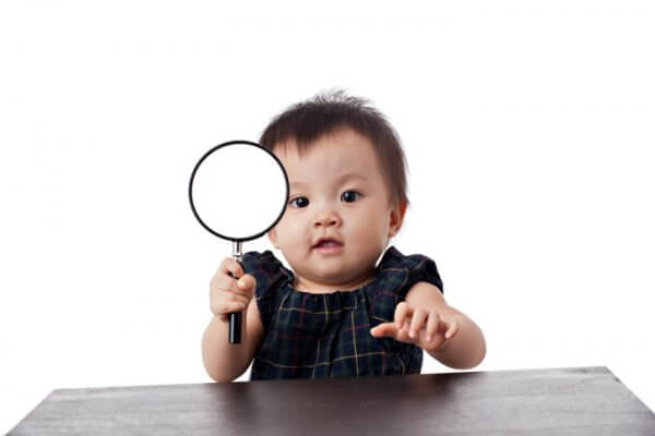 """A very adorable Chinese baby girl holding a magnifying glass, shot with white background.See more of her photos"""